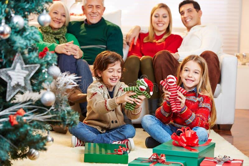 Los niños son felices con los regalos en la Nochebuena fotografía de archivo