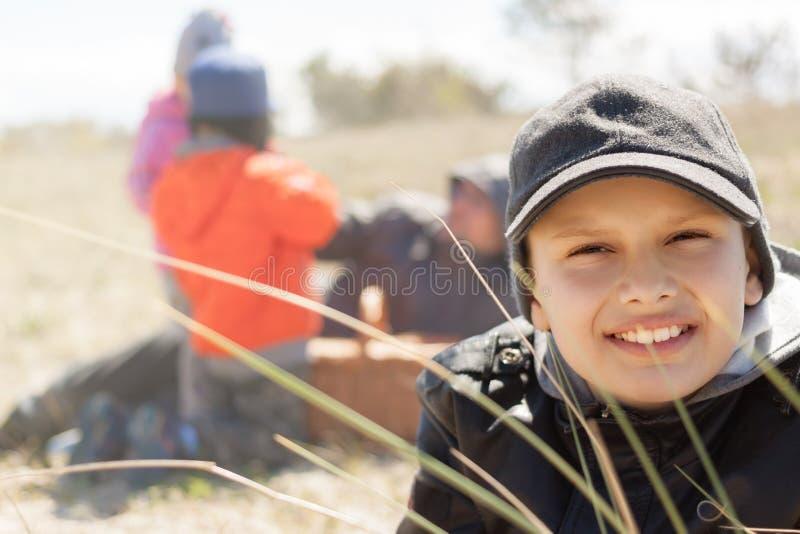 Los niños sonrisa feliz, meriendan en el campo ascendente al aire libre, cercano, mintiendo en la hierba foto de archivo libre de regalías