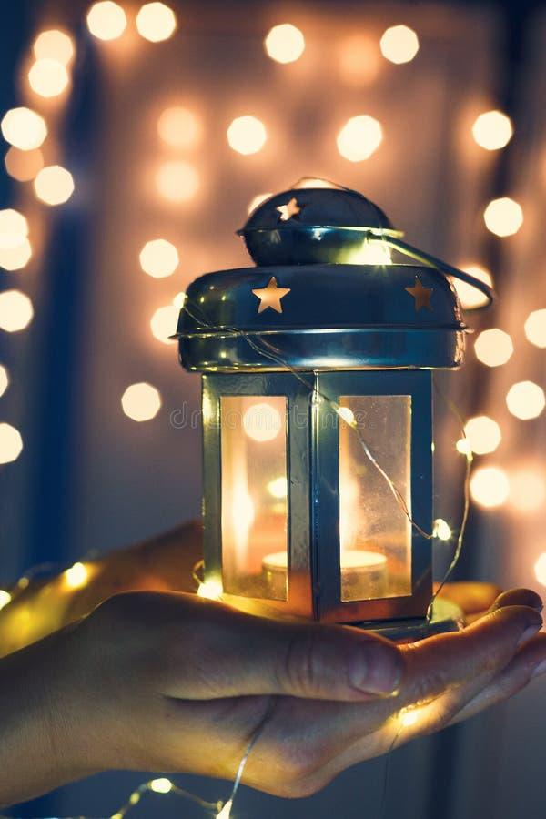 Los niños sostienen la linterna de la Navidad en manos en fondo del bokeh de las luces foto de archivo