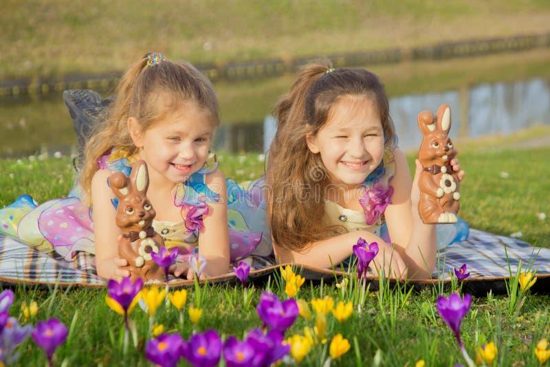 Los niños sostienen pequeños conejos coloridos del chocolate dulce de Pascua fotos de archivo