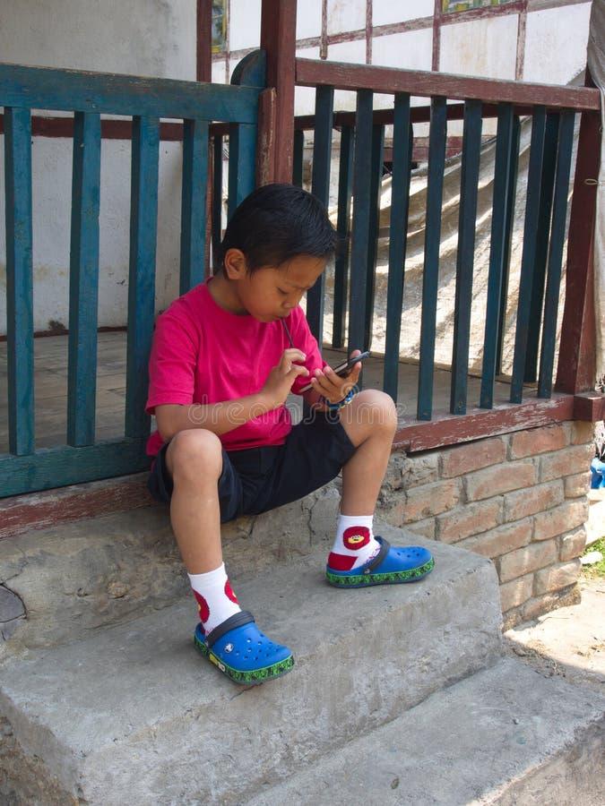 Los niños tibetanos del refugiado de Tíbet están jugando el teléfono móvil en R imágenes de archivo libres de regalías