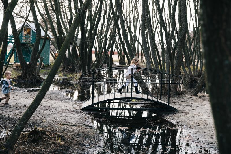Los niños tienen la diversión y funcionamiento a través del puente juego de ni?os cerca del agua niños felices que corren cerca e foto de archivo libre de regalías