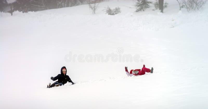 Los niños tienen un rollo en la nieve imagen de archivo