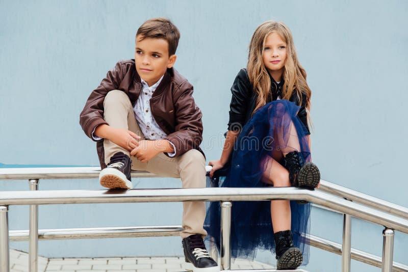 Los niños, un muchacho y una muchacha se están sentando en la verja en los amigos del parque Concepto de amistad fotografía de archivo libre de regalías