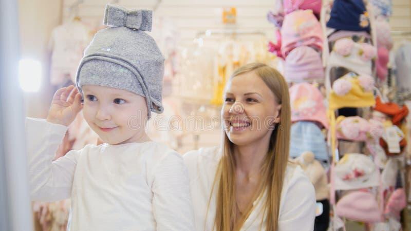 Los niños visten la tienda - pequeño bebé rubio con la madre que hace el sombrero de las compras y de la compra fotos de archivo libres de regalías