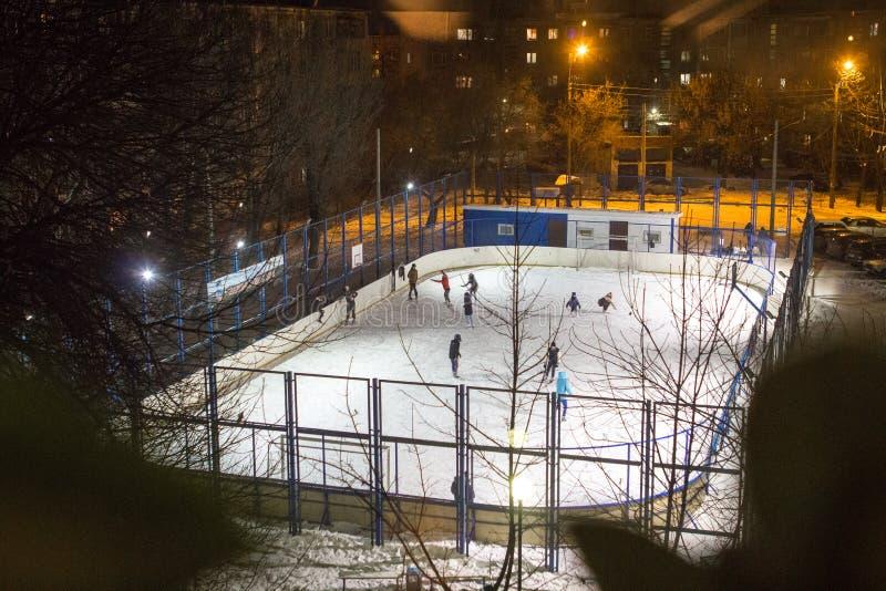 Los niños y los adultos patinan en la pista de hielo en una tarde del invierno foto de archivo libre de regalías