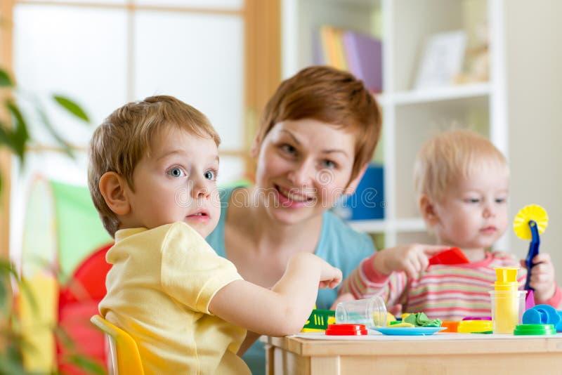 Los niños y la madre que juegan la arcilla colorida juegan en casa foto de archivo libre de regalías