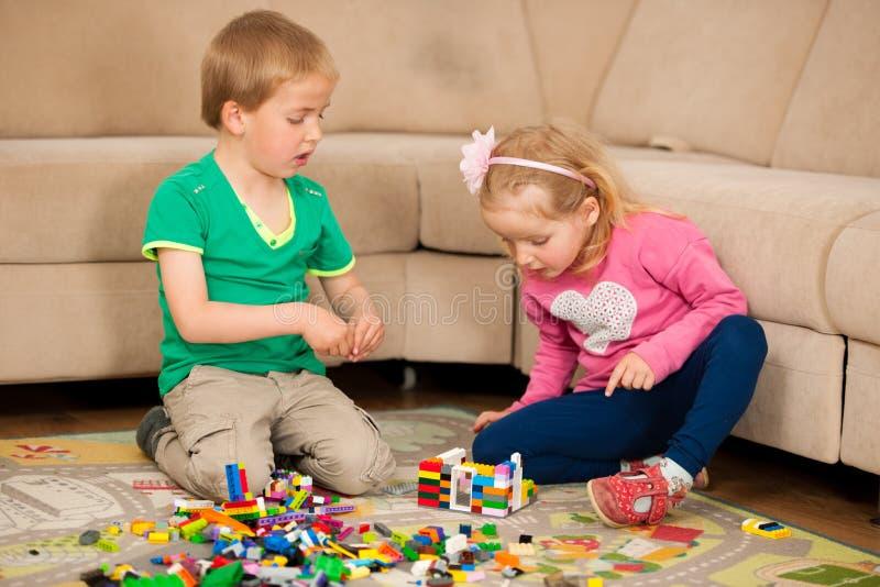 Los niños y su madre están jugando con los bloques en la tierra foto de archivo