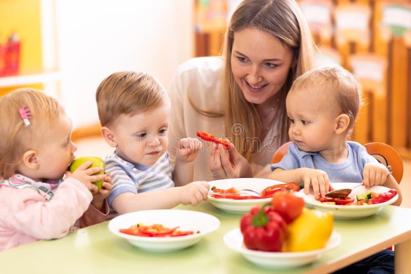 Los ni?os almuerzan en centro de guarder?a Ni?os que comen la comida sana en guarder?a Profesor del cuarto de niños con los bebés fotos de archivo