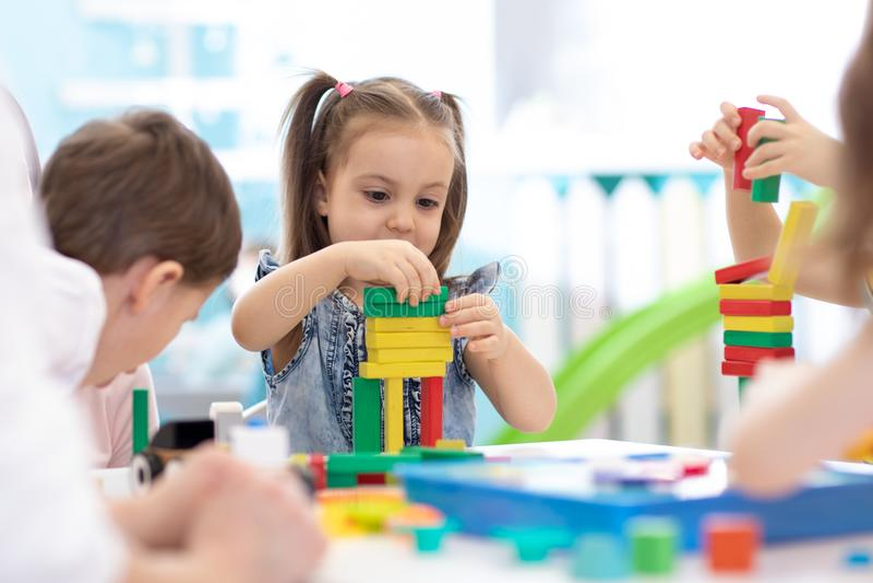 Los ni?os construyen los juguetes del bloque en casa o guarder?a Ni?os emocionales que juegan con los bloques del color Juguetes  fotografía de archivo