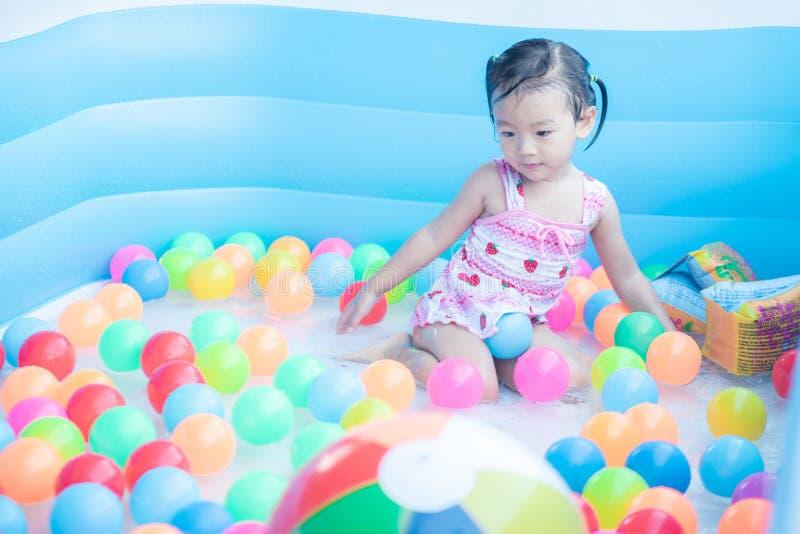 los ni?os disfrutan y se divierten que juega el agua en piscina inflable con colorido de peque?as bolas imágenes de archivo libres de regalías