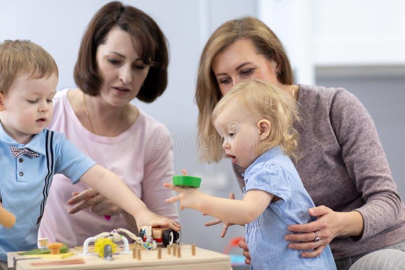 Los ni?os juegan con los juguetes educativos en cuarto de ni?os imágenes de archivo libres de regalías