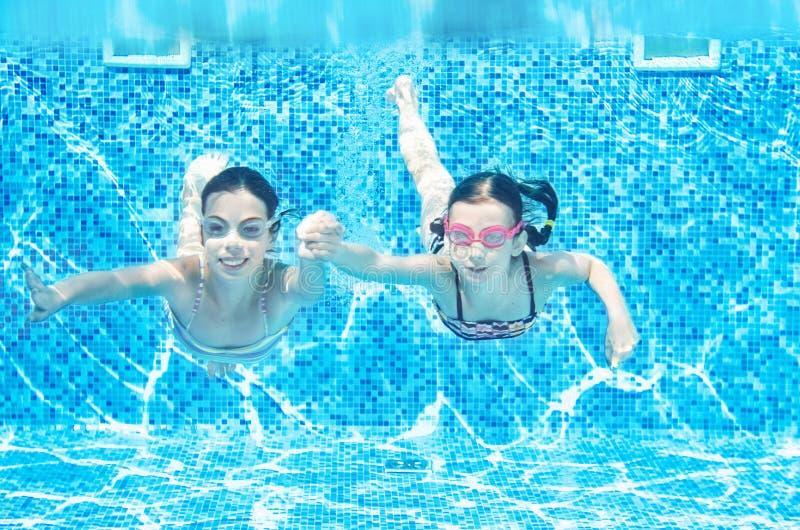 Los ni?os nadan en la piscina subacu?tica, las muchachas activas felices se divierten bajo el agua, la aptitud de los ni?os y dep imagenes de archivo