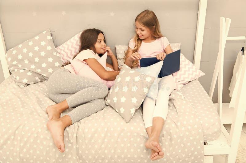 Los ni?os se preparan se van a la cama Dormitorio acogedor del tiempo agradable Los pijamas lindos del pelo largo de las muchacha foto de archivo