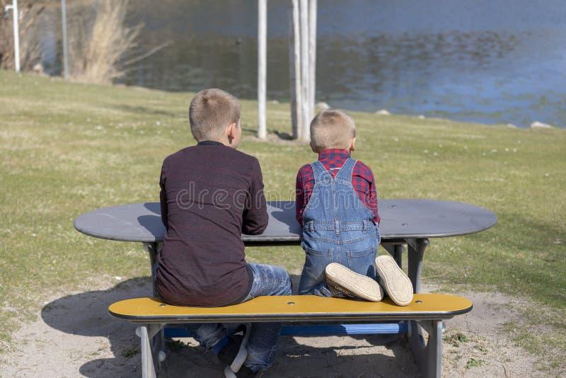 Los ni?os se sientan en un banco de madera en el aire abierto imagen de archivo libre de regalías