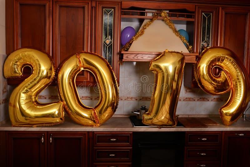 Los nuevo 2019 años están viniendo El grupo de oro que llevaba alegre de la gente joven coloreó números y se divierte en la fiest imagen de archivo libre de regalías