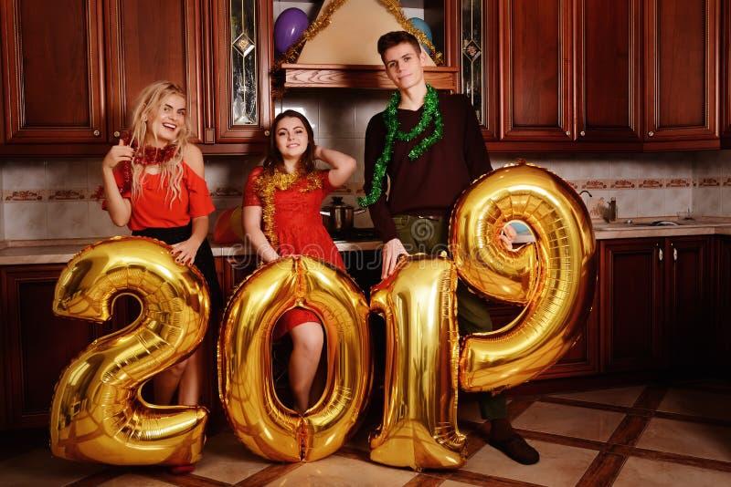 Los nuevo 2019 años están viniendo El grupo de oro que llevaba alegre de la gente joven coloreó números y se divierte en la fiest fotos de archivo libres de regalías
