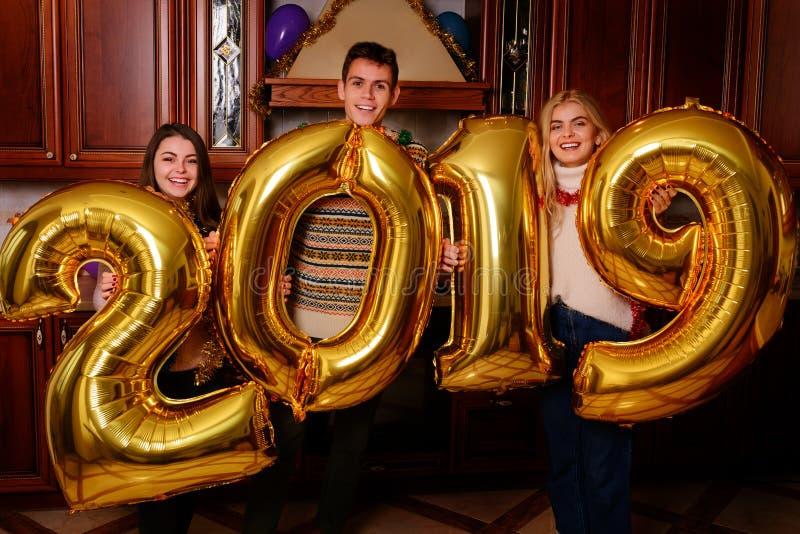 Los nuevo 2019 años están viniendo Grupo de llevar alegre de la gente joven fotos de archivo libres de regalías