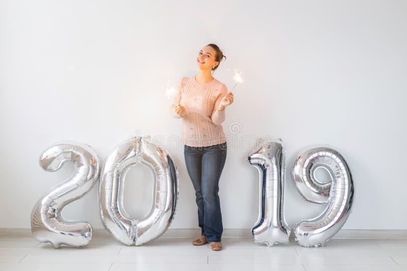 Los nuevo 2019 años son el concepto que viene - situación feliz de la mujer cerca de los números coloreados de plata y de las ben fotografía de archivo