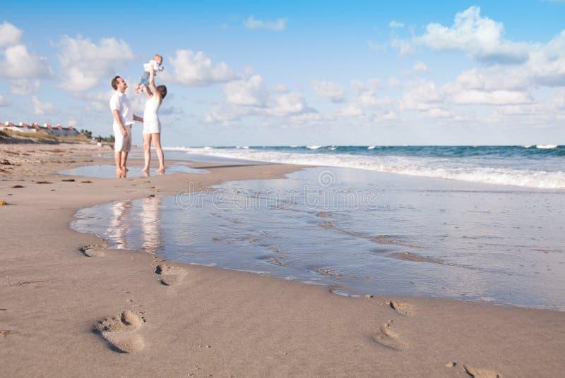 Los nuevos padres juegan con el bebé en la playa fotos de archivo libres de regalías