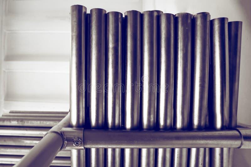 Los nuevos tubos del metal, con la capa plateada cromo, mienten en estantes del almacenamiento Fondos del concepto de la industri fotografía de archivo