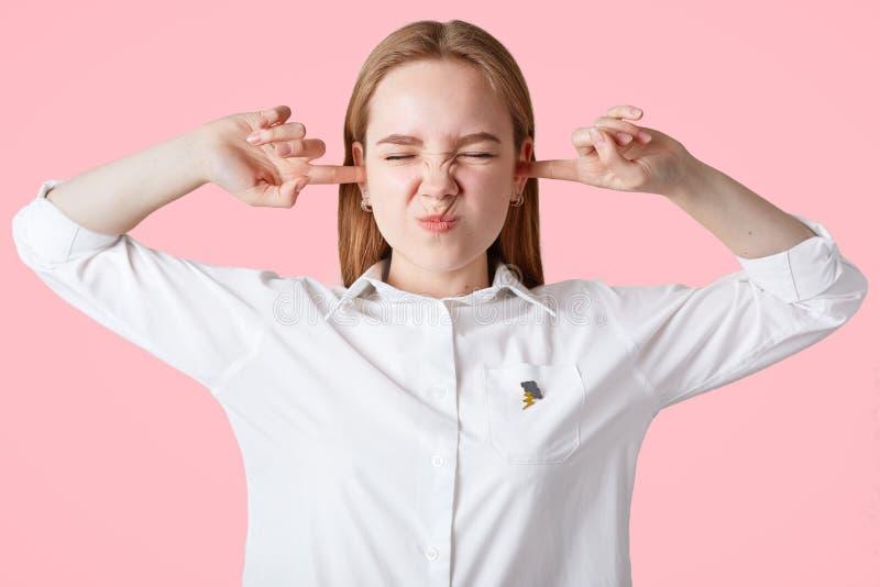 Los oídos caucásicos hermosos enfadados de los enchufes de la hembra con la molestia, oyen el sonido irritado, llevan la camisa b fotos de archivo libres de regalías