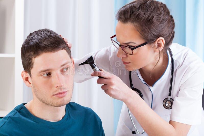 Los oídos del paciente de examen del doctor joven fotos de archivo libres de regalías