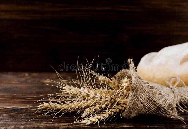 Los oídos del trigo en arpillera se ruedan para arriba imágenes de archivo libres de regalías