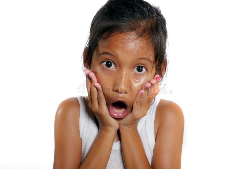 Los 7 o 8 años dulces y lindos del niño femenino chocaron y sorprendieron la boca de apertura con incredulidad y la expresión de  foto de archivo