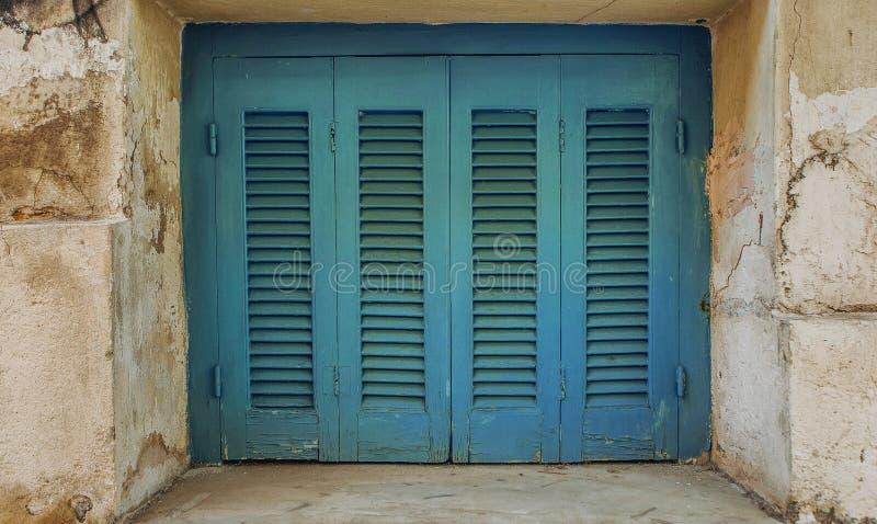Los obturadores de las puertas texturizaron la casa de madera de la piedra vieja foto de archivo libre de regalías