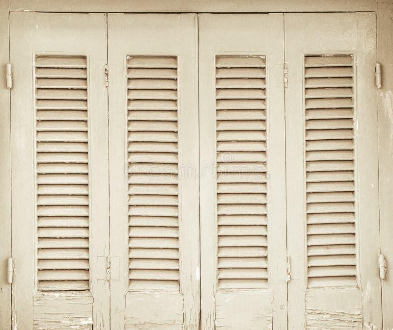 Los obturadores de las puertas texturizaron la casa de madera de la piedra vieja fotos de archivo