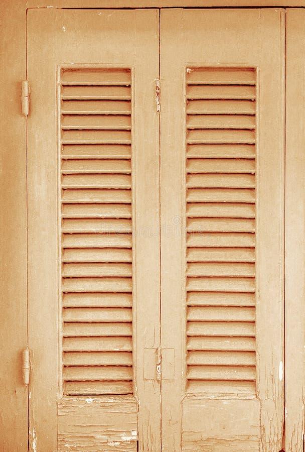Los obturadores de las puertas texturizaron la casa de madera de la piedra vieja foto de archivo
