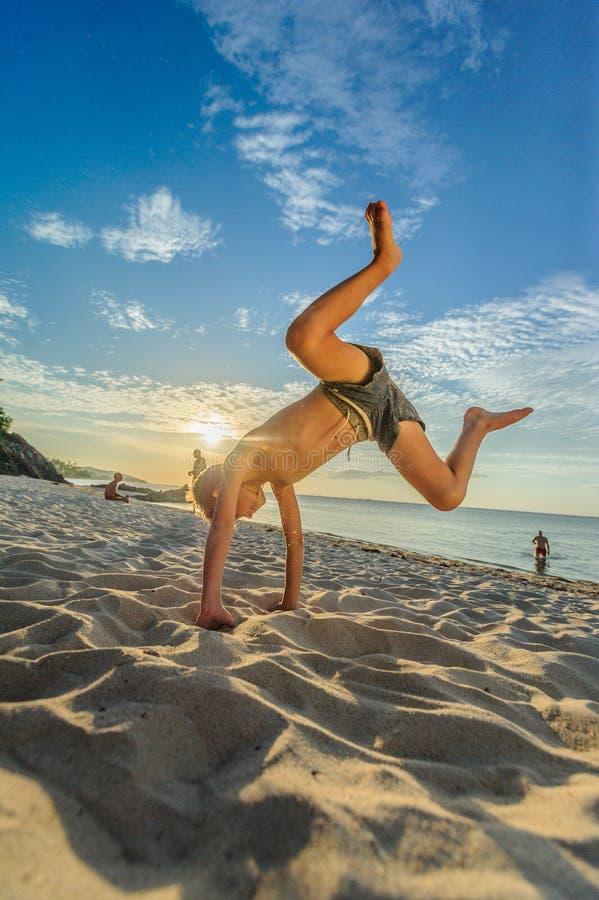 Los ocho años hermosos de muchacho en la playa realizan los bosquejos acrobáticos fotografía de archivo libre de regalías
