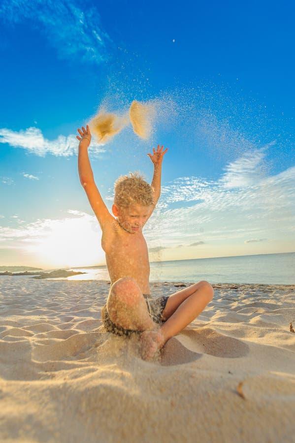 Los ocho años hermosos de muchacho en la playa realizan los bosquejos acrobáticos fotografía de archivo