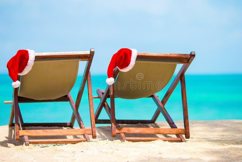 Los ociosos de Sun con el sombrero de Papá Noel en la playa tropical hermosa con la arena y la turquesa blancas riegan Vacaciones fotografía de archivo