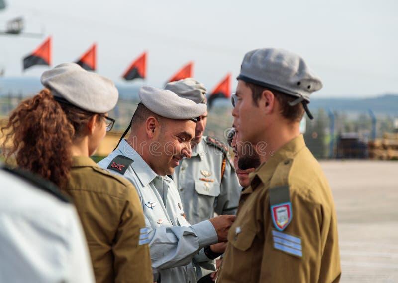 Los oficiales de la CA recompensan al soldado con las insignias en la formación en el monumento conmemorativo caido cuerpo de la  fotografía de archivo
