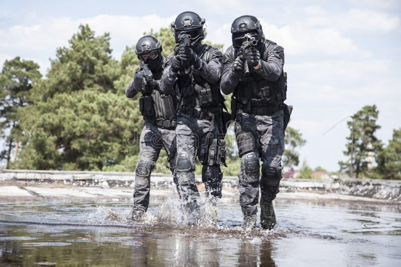 Los oficiales de policía de los ops de espec. GOLPEAN CON FUERZA en el agua fotos de archivo libres de regalías