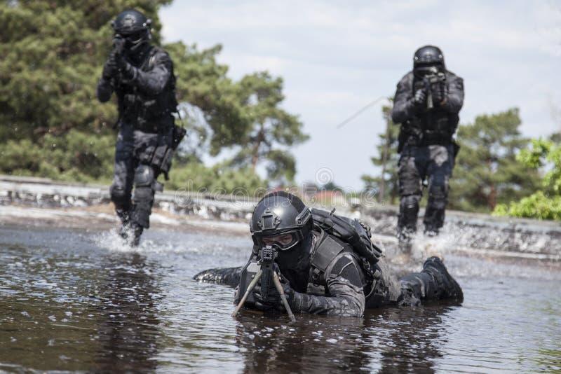 Los oficiales de policía de los ops de espec. GOLPEAN CON FUERZA en el agua foto de archivo