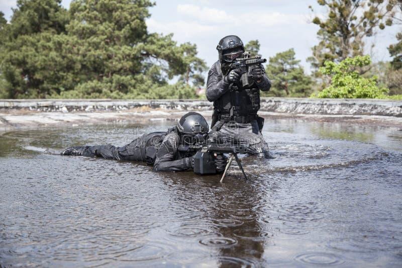 Los oficiales de policía de los ops de espec. GOLPEAN CON FUERZA en el agua fotografía de archivo
