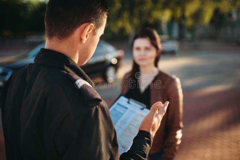 Los oficiales de policía leen ley al conductor femenino fotos de archivo libres de regalías
