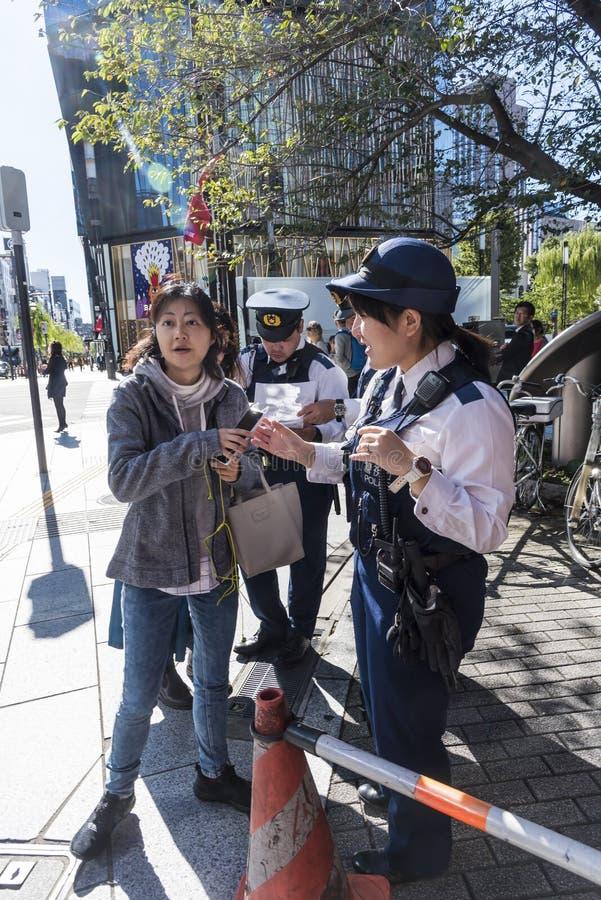 Los oficiales de policía que ayudan a la mujer encuentran la manera Ginza Tokio fotografía de archivo