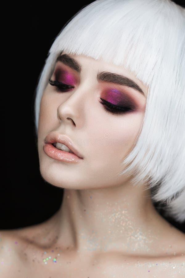 Los ojos ahumados construyen a la mujer rubia joven hermosa con el peinado del volumen Foto de la moda en fondo negro imagenes de archivo