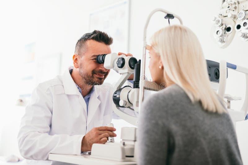 Los ojos de la mujer de examen del óptico con una máquina fotografía de archivo libre de regalías