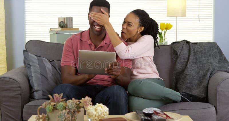 Los ojos de la mujer negra del novio joven de la cubierta como él hojea el web en la tableta imagenes de archivo