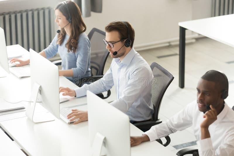 Los operadores de centro de atención telefónica diversos combinan el trabajo en los ordenadores en oficina fotos de archivo
