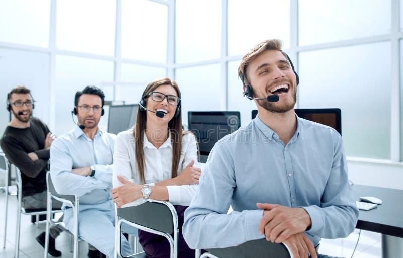Los operadores sonrientes apoyan en el lugar de trabajo imagenes de archivo