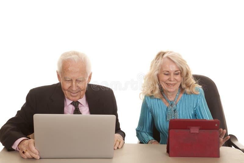 Los ordenadores de empresa mayores de los pares miran abajo fotos de archivo