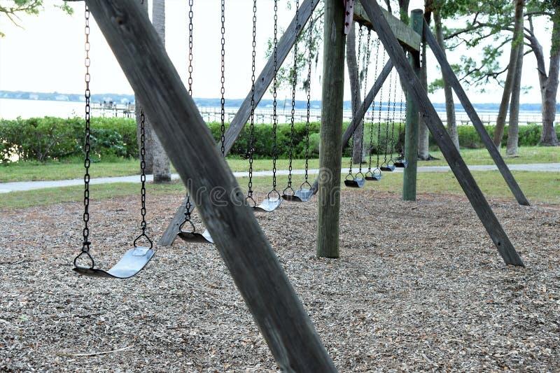 Los oscilaciones abandonados vacíos en un parque local reflejan nuestra niñez olvidada imagenes de archivo