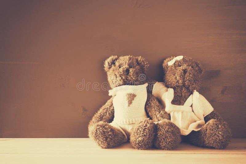 Los osos de peluche lindos juntan el abrazo en la tabla de madera imágenes de archivo libres de regalías