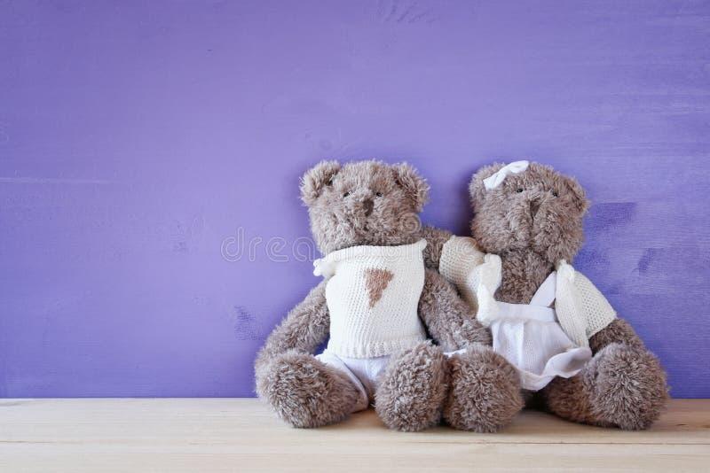 Los osos de peluche lindos juntan el abrazo en la tabla de madera foto de archivo